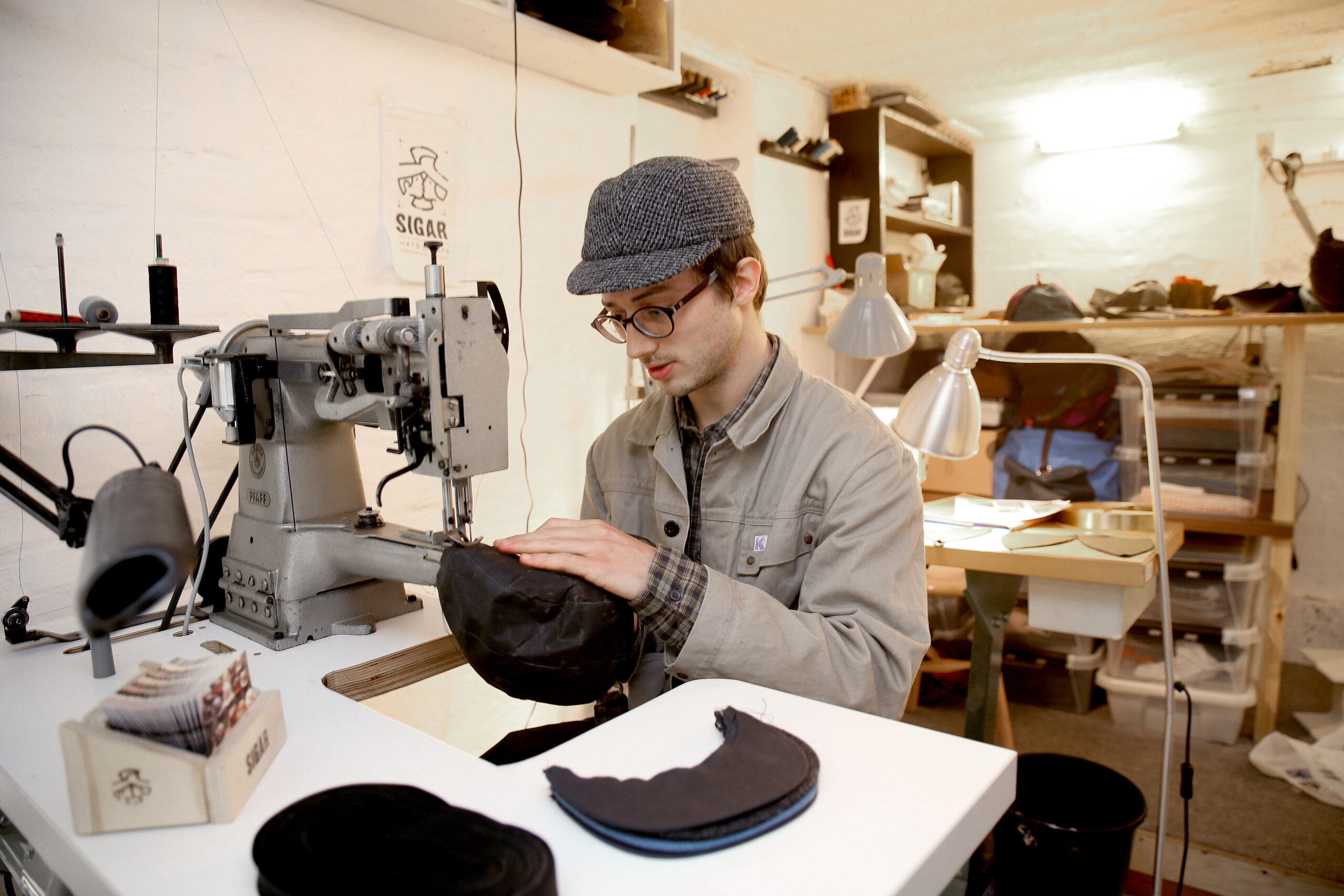 Silas sewing a cap on a freearm industrial sewingmachine