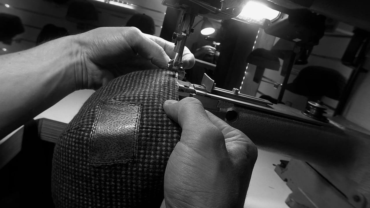 Picture of hands sewing on a cap, in the capmakerworkshop of Wilgart