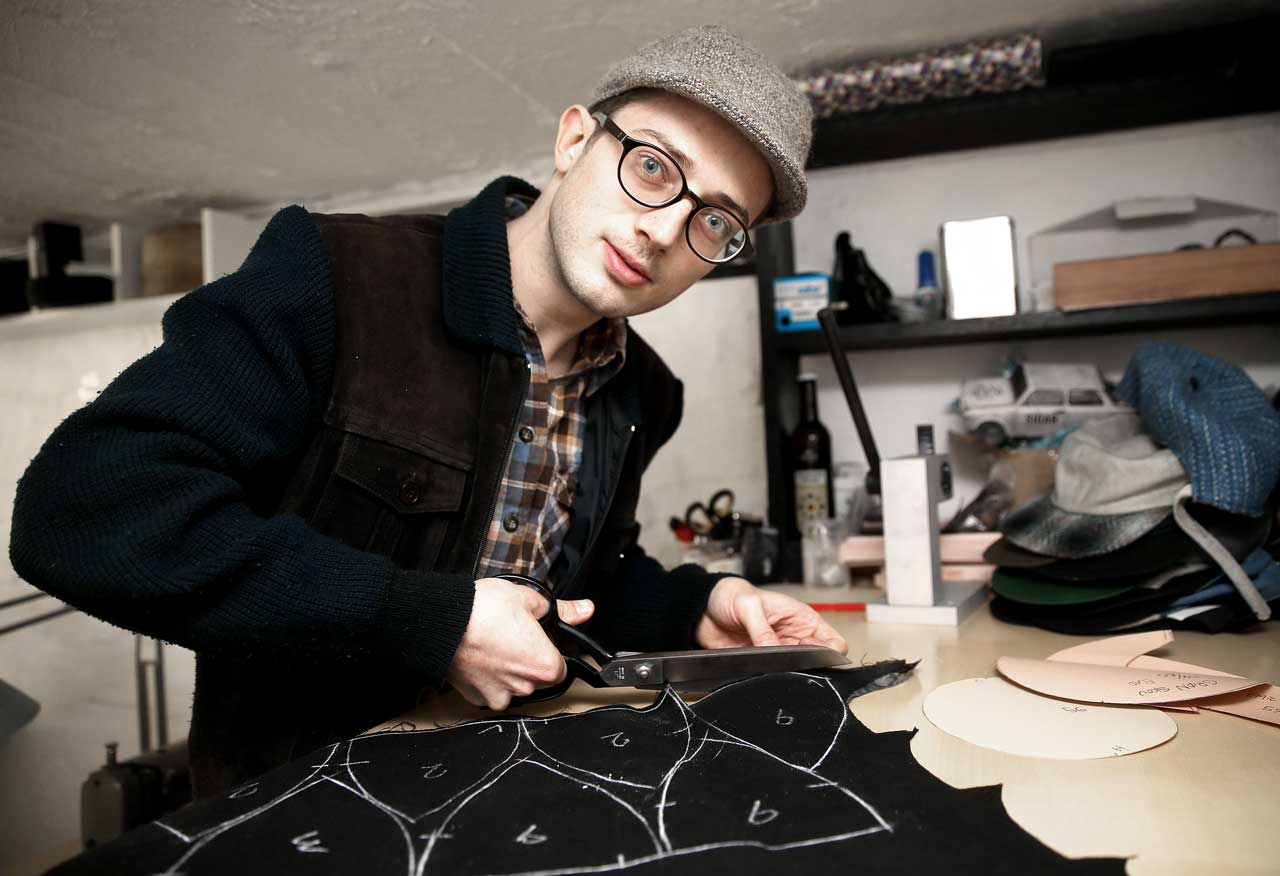 Silas cutting a black wool fabric with a scissor.